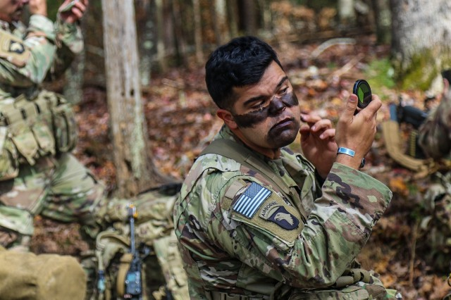 """U.S. Army Capt. Harrison Goluses, company commander, Company C, 326th Brigade Engineer Battalion """"Sapper Eagles"""", 1st Brigade Combat Team, 101st Airborne Division, puts on camouflage face paint in the woods of Dahlonega, Georgia preparing to initiate the start of Bastogne Forge with a 26-hour tactical training event Oct. 27 in Dahlonega, Ga., during the brigade senior leader professional development exercise. The Bastogne Forge exercise took the leadership within 1BCT, 101st Abn Div. on a five day leader development exercise to strengthen bonds through shared hardship and gain a greater understanding of their unit history."""