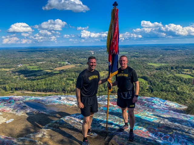 U.S. Army Col. Robert Born, brigade commander, 1st Brigade Combat Team, 101st Airborne Division, left, standing with the brigade colors on top of Currahee mountain with U.S. Army Command Sgt. Maj. Derek Wise, brigade senior enlisted advisor, 1st Brigade Combat Team, 101st Airborne Division, right, after running three miles up the historic trail at Bastogne Forge Oct. 29 in Toccoa, Ga. The Bastogne Forge exercise took the leadership within 1BCT, 101st Abn Div. on a five day leader development exercise to strengthen bonds through shared hardship and gain a greater understanding of their unit history.