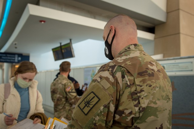 Army Staff Sgt. James Kociencki, Soldier assigned to 105th Military Police Company, Buffalo, N.Y., greets an inbound passenger during flight arrivals at Buffalo-Niagara International Airport, supporting the state's travel advisory Oct. 23, 2020. The team meets arriving passengers to distribute the State Department of Health Traveler form to travelers coming from restricted states. New York Guard Soldiers and Airmen continue to conduct missions in support of the COVID-19 response.