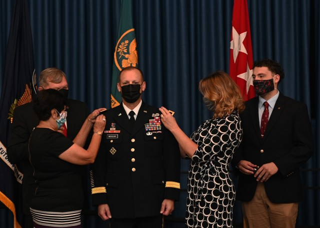 Army Lt. Gen. D. Scott McKean, promoted from Maj. Gen., has his new rank affixed to his jacket by family members during a promotion ceremony at Camp Mabry, Texas, Nov. 2, 2020. Following the promotion, McKean assumed duties as Deputy Commanding General, Army Futures Command and Director, Futures and Concepts Center. McKean thanked family, friends, and Soldiers that helped him along the way, including retired Gen. James D. Thurman, who has known McKean for more than two decades and officiated four of his last five promotion ceremonies. (U.S. Army photo by David Miller)