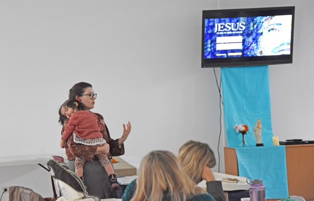 """WIESBADEN, Germany - Dara Quintero, study leader for Catholic Women of the Chapel at U.S. Army Garrison Wiesbaden, speaks to a group of women about the parables of Jesus in relation to the history of church and the """"Our Father,"""" while holding daughter Antonia Oct. 22 at the Hainerberg Chapel."""