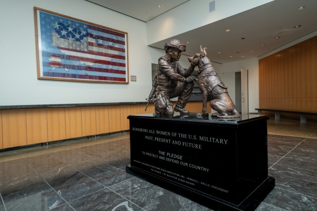 """The Military Women's Memorial unveiled a new monument, titled """"The Pledge,"""" that captures a moment of mutual respect and love between a female handler and her Belgian Malinois in Arlington, Va., Oct. 19, 2020.  The statue depicts a dog reaching up to his handler as she kneels beside the dog."""