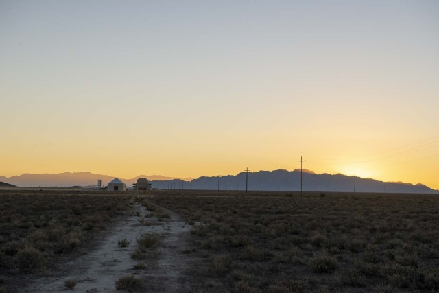 The sun sets on the first Technology Experimentation and Characterization Field Trials (TECFT) held at Dugway Proving Ground. The Active Standoff Chamber (left) and the Joint Ambient Breeze Tunnel (right) can be seen in the distance. Both are unique to the West Desert Test Center and were utilized during the first week of the TECFT event to test new detection technologies.