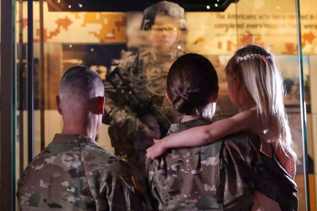 """Lt. Col. Ashley Hartwell, a reservist, looks at a life-sized model in her visage on display at the National Museum of the U.S. Army, in Fort Belvoir, Va. She was joined by her husband, Maj. Kristopher Hartwell, and daughter, Grace, during the visit. The model, titled """"Corporal on Patrol in Ramadi,"""" highlights the growing role of women in combat during the wars in Iraq and Afghanistan."""