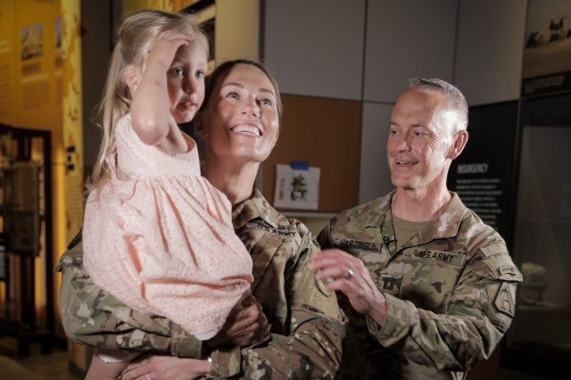 """Lt. Col. Ashley Hartwell, a reservist, looks up in excitement at a life-sized model in her visage on display at the National Museum of the U.S. Army, on Fort Belvoir, Va. She was joined by her husband, Maj. Kristopher Hartwell, and daughter, Grace, during the visit. The model, titled """"Corporal on Patrol in Ramadi,"""" highlights the growing role of women in combat during the wars in Iraq and Afghanistan."""