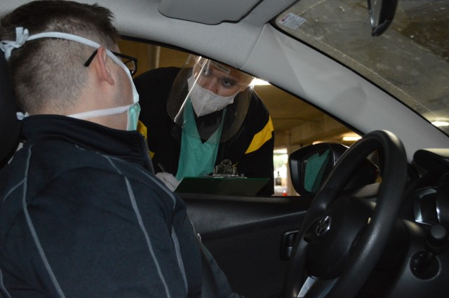 Spec. Diego Timoteo, an Army Combat Medic at Brooke Army Medical Center, Joint Base San Antonio - Fort Sam Houston, Texas, checks an incoming patient at BAMC's drive-through COVID-19 testing area. Timoteo, a native of Brazil, recently earned his American citizenship. (U.S. Army photo by Daniel J. Calderón)