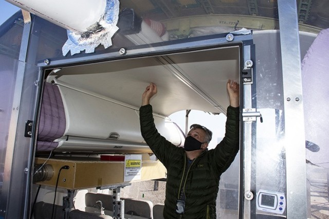 Test Officer Angelo Madonna explains how outside air passes along the vent across the top of the fuselage's ceiling and is distributed to the passengers in seats. Each passenger may also adjust personal airflow with an overhead knob; this will also be studied.