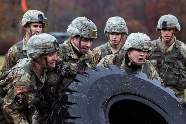 Cadets from the Company H-4 team try to flip a tire during the Team Challenge Event Friday at the Fall Sandhurst Competition. The Team Challenge Event includes the tire flips, aHigh Mobility Multipurpose Wheeled Vehicle(HMMWV)push/pull and log squats. (U.S. Army Photo by CDT Nicholas Mackey)