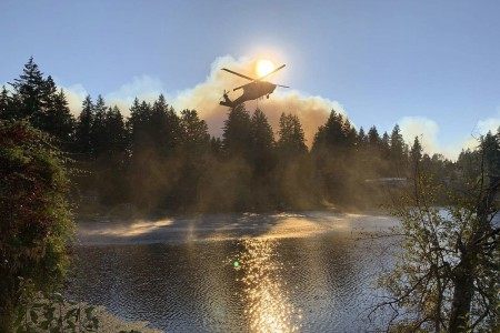 A Washington Army National Guard Black Hawk helicopter gathers water in a bucket to help battle a wildfire near Bonney Lake, Wash., Sept. 9, 2020.