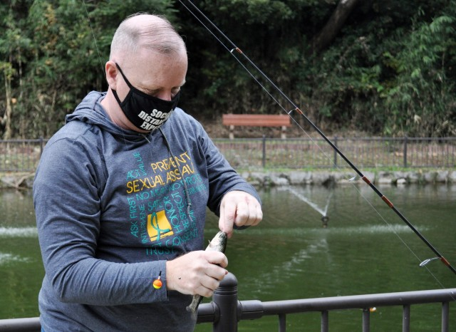 Tony Bean removes a hook from the mouth of a trout during the Community Trout Fishing Derby at Camp Zama, Japan, Nov. 7.