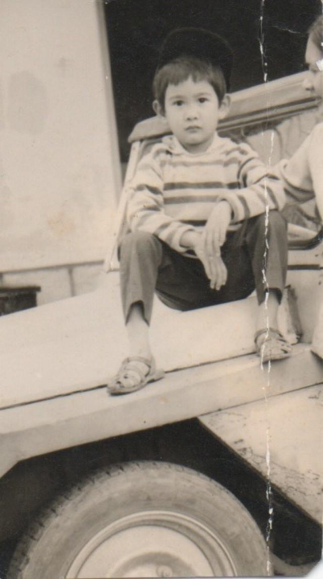 Lan Dalat rests on the family Citroen in Vietnam.
