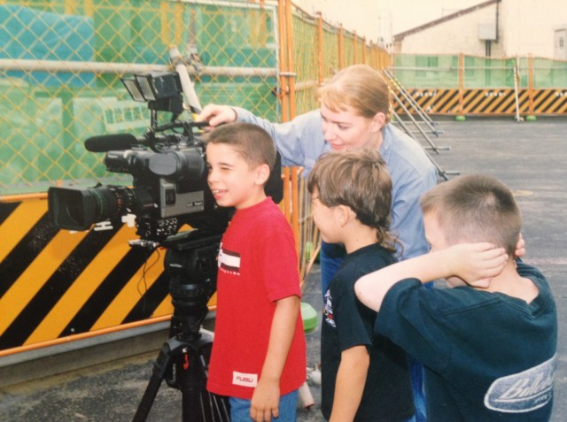 Navy Journalist Ellen (Maurer) Crown lets local military school children on Misawa Air Base, Japan, look through the lens of her broadcast camera during a video shoot, while she was assigned to the Armed Forces Radio and Television Service in 1999. (Photo courtesy Ellen Crown)