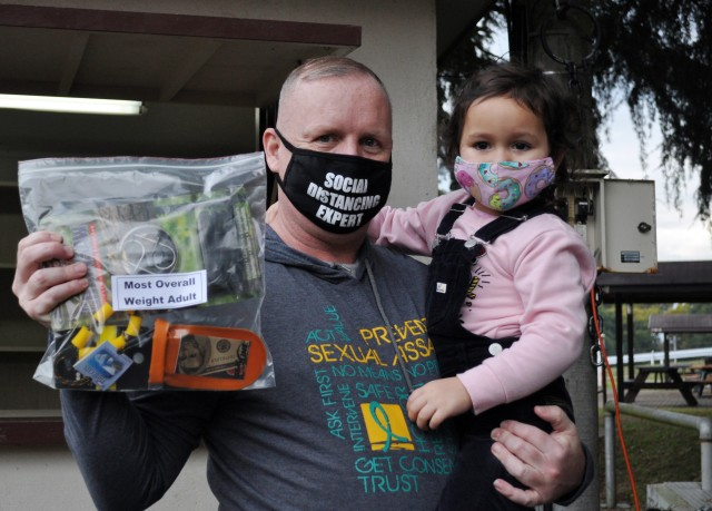 Tony Bean and his daughter Elena, 3, pose for a photo after winning an award during the Community Trout Fishing Derby at Camp Zama, Japan, Nov. 7.