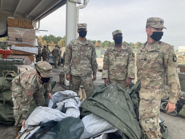 Specialist Daniella Valverde, left, Pfc. Jawun Perry, Sgt. Vincent Thomas and Spec. Jon Adrian, all of 526th Brigade Support Battalion, 2nd Brigade Combat Team, 101st Airborne Division (Air Assault) fold tarps as they go through storage items Nov. 5 as part of Operation Clean Eagle, , the 101st Airborne Division's postwide cleanup effort designed to enhance readiness and quality of life by properly main-taining Fort Campbell's training and cantonment areas.