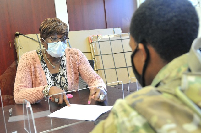 Patsy Piggott, Army Emergency Relief specialist, works with a client during a meeting Nov. 17 at Army Community Service headquarters. ACS, the Army's social services arm, has ramped up its services as a result of COVID-19.