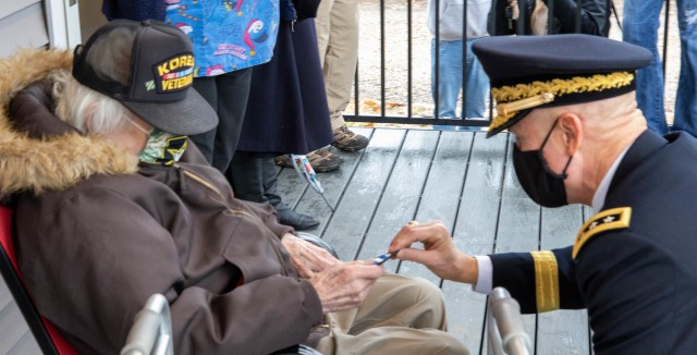 Korean War veteran J.P. Whitaker receives a 3rd Infantry Division patch from First Army Commanding General, Lt. Gen. Thomas James Jr., during a ceremony welcoming Whitaker back to his refurbished home in Davenport, Iowa. Whitaker and James are both 3rd ID veterans.