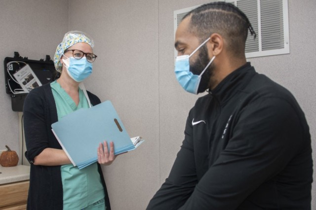 Alfiya Mityukova, a registered nurse, and Roderick Johnson, a research assistant, demonstrate patient screening for the Operation Warp Speed COVID-19 vaccine trial at Brooke Army Medical Center, Fort Sam Houston, Texas, Nov. 16, 2020. BAMC and Wilford Hall Ambulatory Surgical Center are participating in the Phase III trial to evaluate the vaccine under development by AstraZeneca as part of a national initiative to accelerate the development, production and distribution of COVID-19 vaccines, therapeutics and diagnostics.