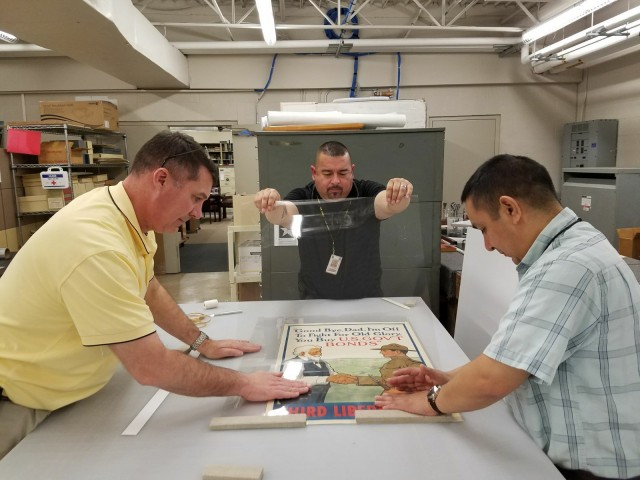 Museum Specialist Chris Goodrow, Exhibit Specialist Lupe Perez, and Archivist Carlos Alvarado work on the finishing touches for featured posters on display in the WWI Gallery Exhibit at the U.S. Army Medical Department Museum. Photo courtesy of Francis Trachta, AMEDD Museum.