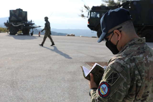 U.S. Army Sfc. Pablo Rodriguez, a patriot missile operator assigned to the 10th Army Air and Missile Defense Command and an evaluator for NAMFI 20, observes German airmen here on Nov. 17, 2020 at the NATO Missile Firing Installation(NAMFI). NAMFI is a German led, Greece hosted installation and supported by The Netherlands. The NAMFI live fire takes place on the Greek Island of Crete and is conducted by over 600 personnel from the U.S., Greece, Germany and the Netherlands; and provides invaluable experience to participants by giving them a chance to build partnership as well experience in a multinational environment. (U.S. Army Photo by Sgt. Vincent Wilson)