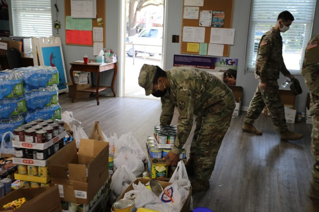 Spc. Flores Jimenez, Headquarters and Headquarters Company, 504th Expeditionary Military Intelligence Brigade, sets donated nonperishable food down, Nov. 20, 2020, Nolanville, Texas. The brigade donated 4,874 lbs. during this event. (U.S. Army photo by Tyler Tanaka)