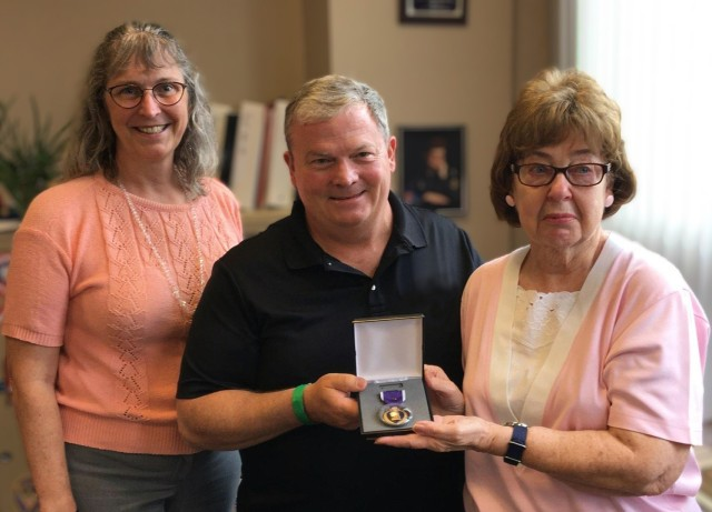 Bob Healy, recovery care coordinator at Fort Drum, and Theresa Neibacher, Jefferson State veteran service director, presented Suzanne Adderley with replacements for medals her late husband, Pfc. Charles Farney, was awarded during his service in the Korean War. The original medals were lost in a house fire. (Photo courtesy of Judy Hamm)