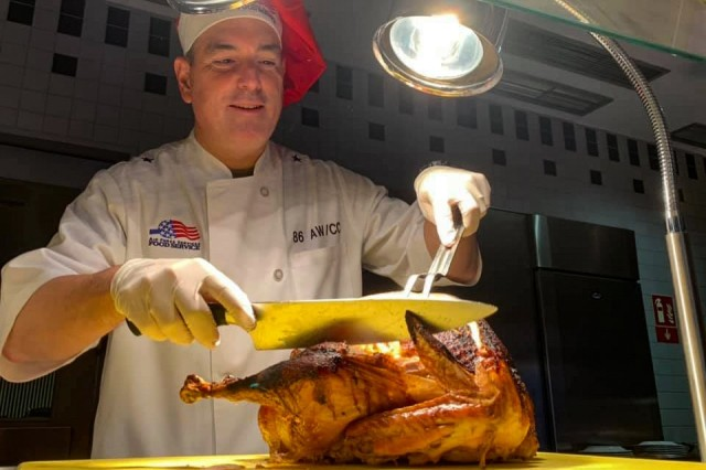 Air Force Brig. Gen. Mark R. August, 86th Airlift Wing commander, gets ready to carve a turkey in the dining facility at Ramstein Air Base, Germany, Nov. 28, 2019. August was part of the leadership team that served Thanksgiving lunch to approximately 300 airmen at the dining facility.