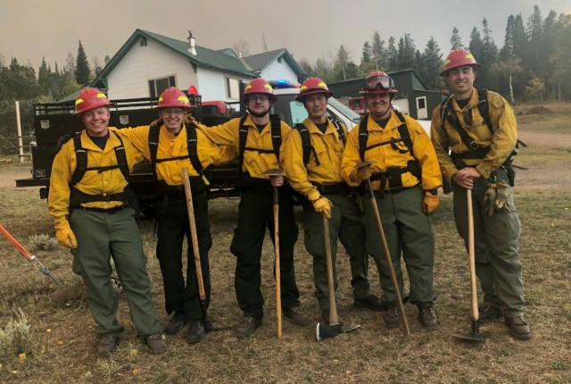 Cadet James Spear, (second from left), protecting a home while fighting the Mullen Fire
