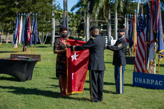 Command Sgt. Maj. Scott A. Brzak, U.S. Army Pacific's command sergeant major; holds the 2-Star flag for Maj. Gen. Timothy M. McKeithen, deputy commanding general-Army National Guard and his wife, Simone, to case the colors during McKeithen's retirement ceremony Dec. 1 held at Historic Palm Circle, Fort Shafter, Hawaii.  McKeithen served over 34 years of service in the U.S. Army.  (U.S. Army photo by Sgt. 1st Class Monik Phan)