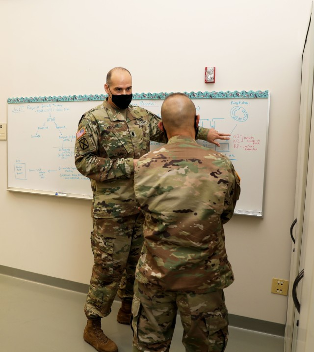 Lt. Col. Gerald Kellar, acting chief of the Public Health Command-Pacific COVID-19 Testing Surveillance Program at Joint Base Lewis-McChord, Washington, explains the command's new COVID-19 pooled testing procedures to Brig. Gen. Jack M. Davis, commanding general of Regional Health Command-Pacific, at PHC-P's new COVID-19 Surveillance Testing Laboratory, Dec. 3, 2020. (U.S. Army photo by Christopher Larsen, RHC-P Public Affairs)