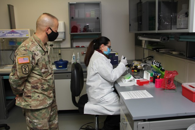 Milagros Sola, a microbiologist with Pubic Health Command-Pacific, works with ribonucleic acid, or RNA, while demonstrating the command's new COVID-19 pooled testing procedures to Brig. Gen. Jack M. Davis, commanding general of Regional Health Command-Pacific, at PHC-P's new COVID-19 Surveillance Testing Laboratory, Dec. 3, 2020. (U.S. Army photo by Christopher Larsen, RHC-P Public Affairs)