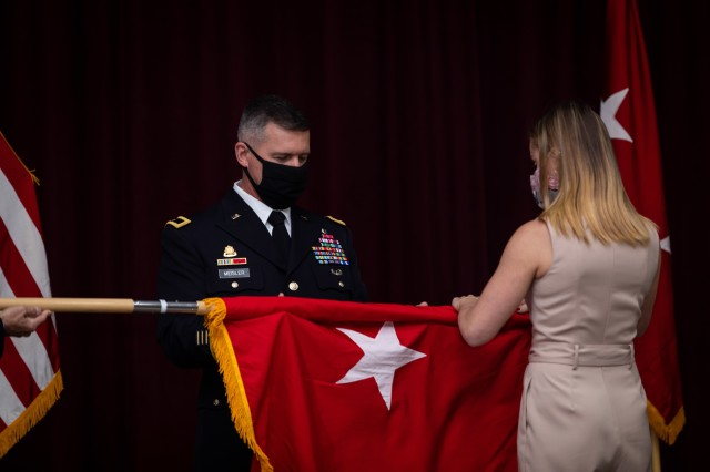 U.S. Army Reserve Brig. Gen. Kevin Meisler unfurls his general officer's flag with his daughter Mackenzie during his promotion ceremony at Joint Base San Antonio-Fort Sam Houston Dec. 5, 2020. With the promotion, Meisler will take command of the 4th Sustainment Command (Expeditionary), which directs more than 6,500 Army Reserve Soldiers throughout Texas, Oklahoma, Arkansas, and New Mexico. (U.S. Army photo by Capt. David Gasperson)