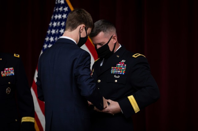 Sean Meisler helps his father U.S. Army Reserve Brig. Gen. Kevin Meisler put on his General Officer's belt during his promotion ceremony held at Joint Base San Antonio-Fort Sam Houston Dec. 5, 2020. (U.S. Army photo by Capt. David Gasperson)