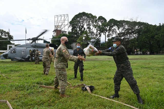 A Honduran Air Force Airman tosses a food bundle to a soldier assigned to Joint Task Force-Bravo at San Pedro Sula, Honduras, Nov. 23, 2020. At the request of the government of Honduras, Joint Task Force-Bravo is providing aerial support to relief operations in Honduras, impacted by Hurricane Iota. (U.S. Air Force Photo by Tech. Sgt. Jael Laborn)