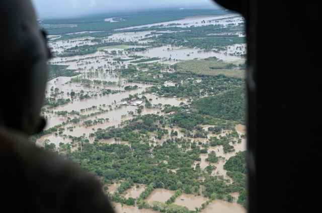 Black Hawk helicopter crew member assigned to the 1-228th Aviation Regiment, Joint Task Force-Bravo looks at a village still under water from Hurricane Iota near San Pedro Sula, Honduras, Nov. 23, 2020. At the request of the government of Honduras, Joint Task Force-Bravo is providing aerial support to relief operations in Honduras, impacted by Hurricane Iota. (U.S. Air Force Photo by Tech. Sgt. Jael Laborn)