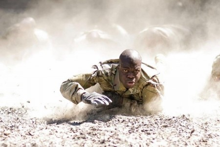 """A determined trainee low crawls through the dust as he makes his way through the """"Team Week"""" confidence course during Basic Combat Training on Fort Jackson, S.C."""