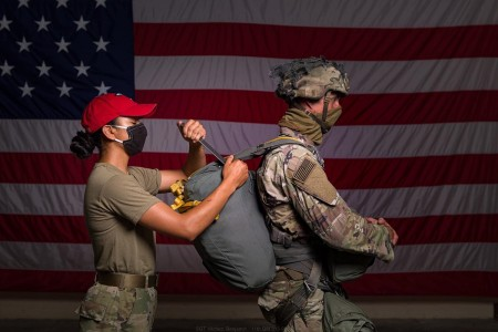 A Soldier assists in the laborious and delicate art of rigging and packing a parachute.