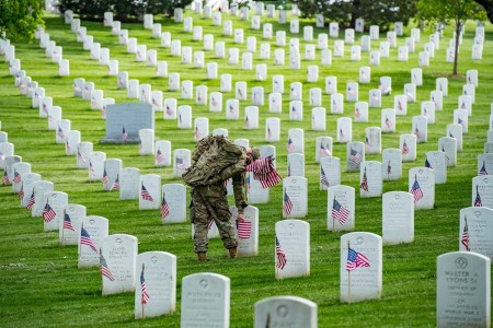 A Soldier from the 3d U.S. Infantry Regiment (The Old Guard) places U.S. flags at headstones as part of Flags-In at Arlington National Cemetery, Arlington, Va., May 21, 2020.