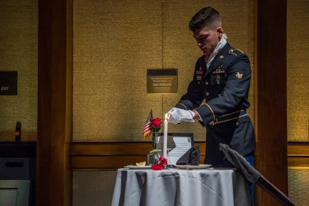 Spc. Brendon McCormick lights the candle at the Prisoner of War/Missing in Action table at Hilton Hawaiian Village, Hawaii, Jan. 16, 2020.