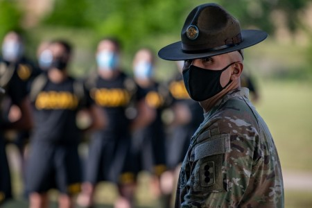 A drill sergeant watches over trainees as they stand in formation while wearing masks and maintaining physical distancing during reception before entering basic combat training May 14, 2020, on Fort Sill, Okla.