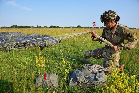 After months of restriction due to Covid-19, a U.S. Army Paratrooper secures her equipment after an airborne operation from a C-130 Hercules aircraft at Rivolto Italian Air Force Base, Udine Italy, June 24, 2020.