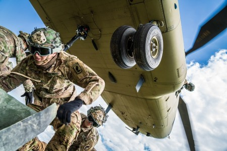 """A crew chief with B Co. """"Big Windy,"""" 1-214th General Support Aviation Battalion relays vital position information back to the CH-47 Chinook pilot from his side window as paratroopers hook their pallet of equipment to the underside of the helicopter."""