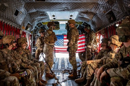 1st Lt. Ismeal Orozco conducts the oath of re-enlistment to Spc. James Carico during a re-enlistment ceremony on a CH-47 Chinook helicopter hovering over Oahu, Hawaii, June 22, 2020.