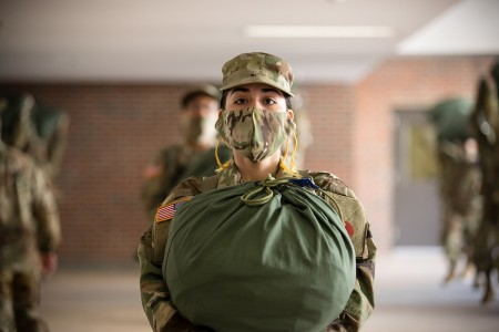 A trainee stands holding a bag full of her issued items after meeting her unit's drill sergeants for the first time at Fort Jackson, S.C., April, 26, 2020.