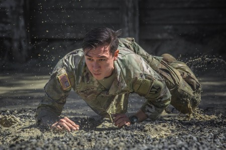 A cadre member with 1st Battalion, 61st Infantry Regiment demonstrates how to go through an obstacle at the Fort Jackson, S.C., Fit to Win 2 course, April 28, 2020.