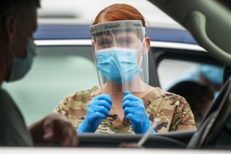 Delaware Army National Guard Pfc. Kelly Buterbaugh gives instructions to a motorist during a drive-thru coronavirus testing mission at the University of Delaware's Science, Technology and Advanced Research Campus in Newark, Del., May 29, 2020.
