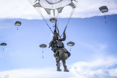 Army paratroopers descend after jumping from a C-17 aircraft during training at Andersen Air Force Base, Guam, June 30, 2020, as part of Spartan Flex, a joint capabilities exercise in the Indo-Pacific region.