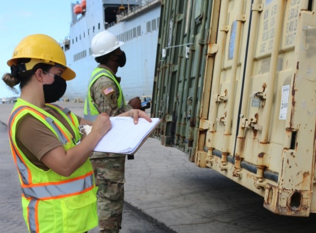 Petty Officer Ilene Cerda and Staff Sgt. Deontre Austin take the numbers off of containers as they are offloaded from the USNS Fisher at Pearl Harbor on Dec. 3.