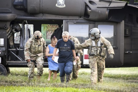 Army HH-60 Black Hawk helicopter crew members escort rescued U.S citizens at San Pedro Sula, Honduras, Nov. 7, 2020, in the aftermath of Hurricane Eta.