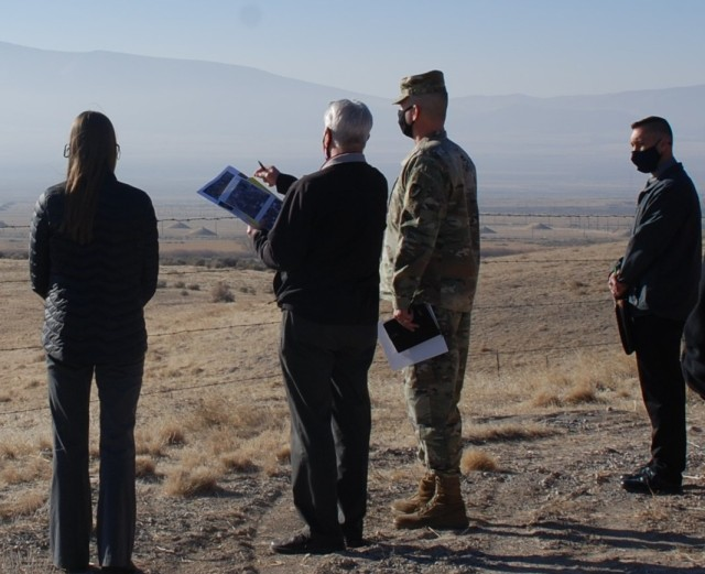 Civilians and soldier looking over high desert valley.