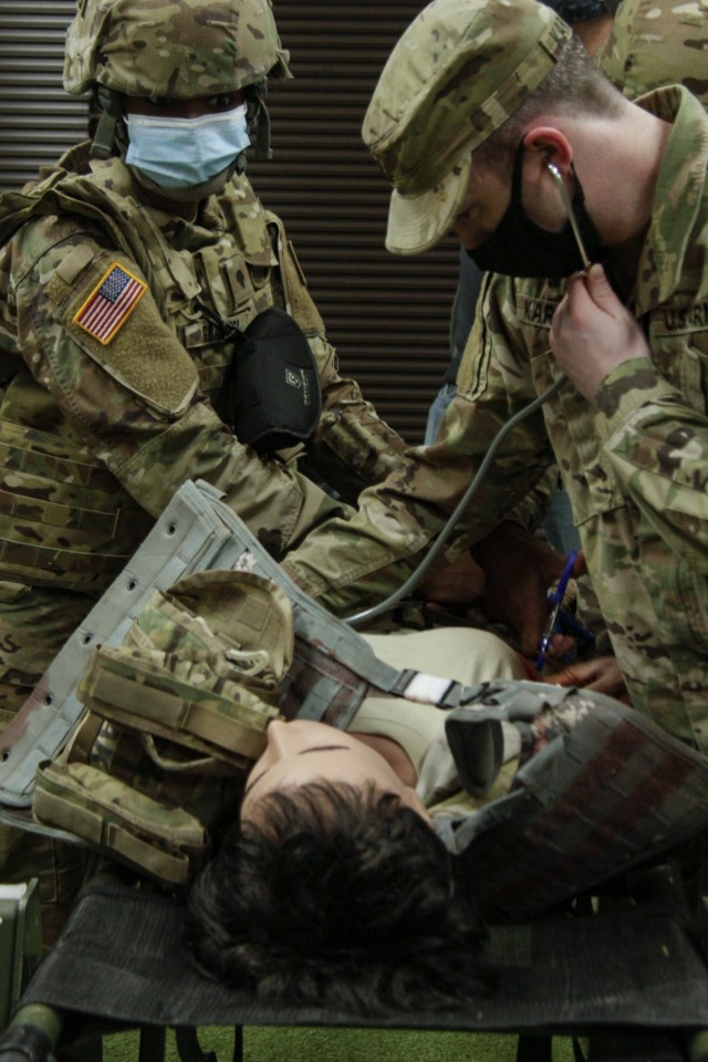 Capt. Daniel Karakas (right), a medical corps officer at Winn Army Community Hospital, checks a trial female mannequin for breathing, while Spc. Ekya Graham, an aviation operation specialist assigned to 2nd Battalion, 3rd Aviation Regiment, holds pressure on a wound to stop bleeding at the Medical Simulation Training Center on Fort Stewart, Georgia, Dec. 2, 2020. The training required the Soldiers to remove clothing from the mannequin's torso to feel around the breast for an entry wound and apply a chest seal. (U.S Army photo by Pfc. Aaliyah Craven)